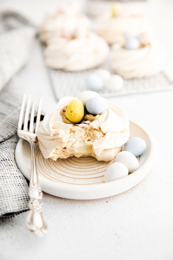 an Easter Meringue Nest on a small white plate with a bite taken out