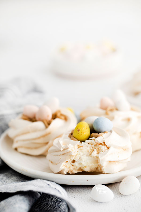 Easter Meringue Nests on a white plate with a bite taken out of one