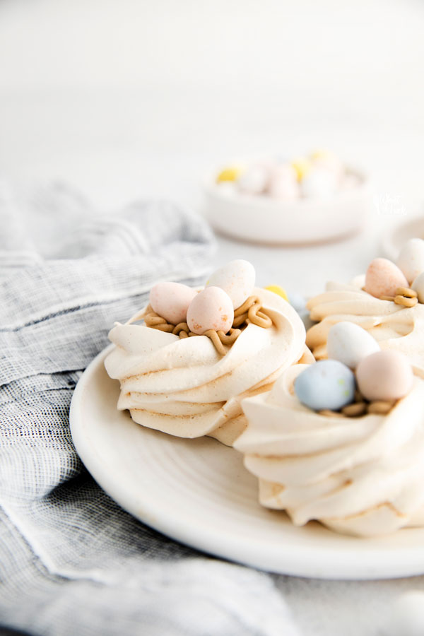 Easter Meringue Nests on a white plate with Mini Cadbury Eggs on top and in the background