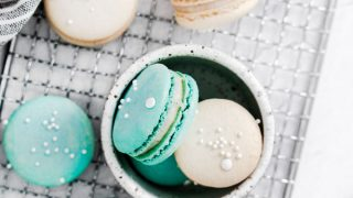 overhead shot of white and blue macarons on a wire rack and in a small white bowl