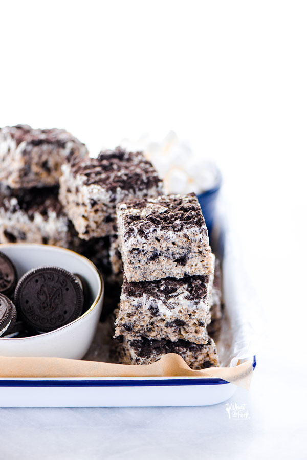 Gluten Free Cookies and Cream Rice Krispie Treats stacked on an enamel tray lined with unbleached parchment paper