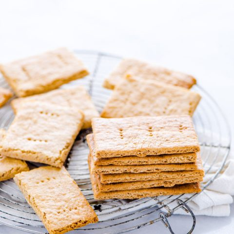 gluten free graham crackers stacked and piled on a round wire metal cooling rack