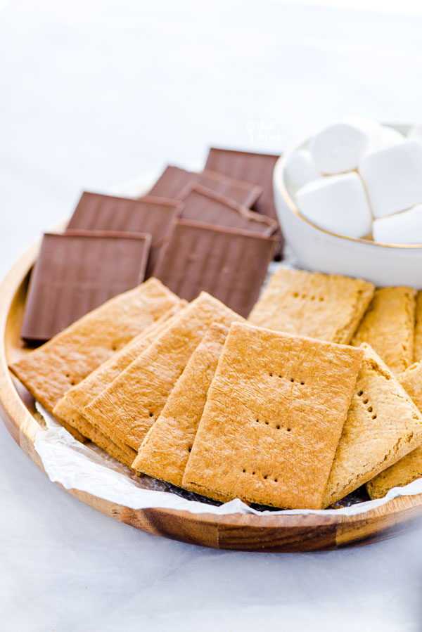 gluten free graham crackers on a round wood tray with chocolate bars and marshmallows