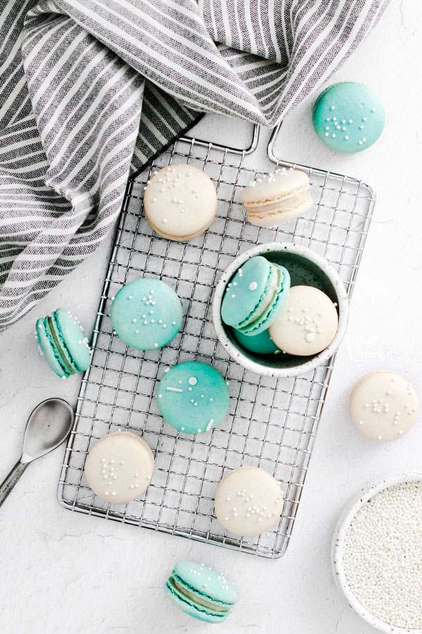 overhead shot of white and blue French Macarons on a small wire rack