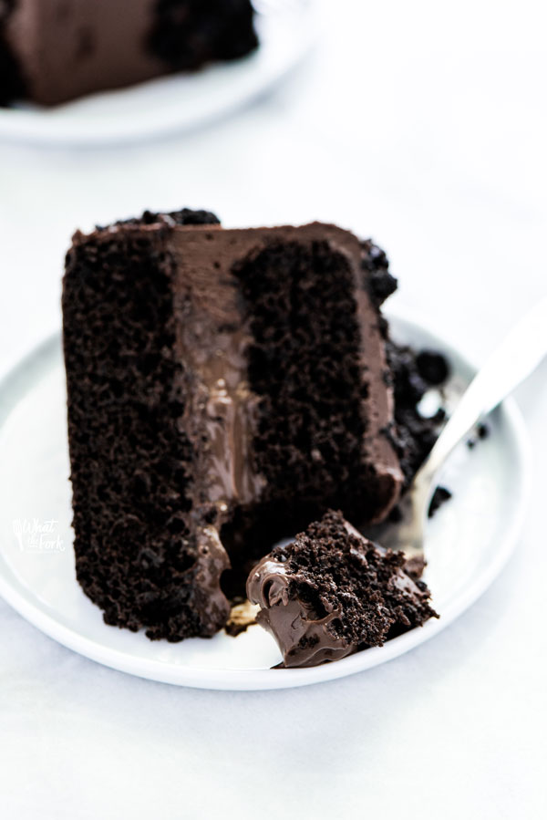 a slice of Gluten Free Brooklyn Blackout Cake on a white plate with a piece on a fork
