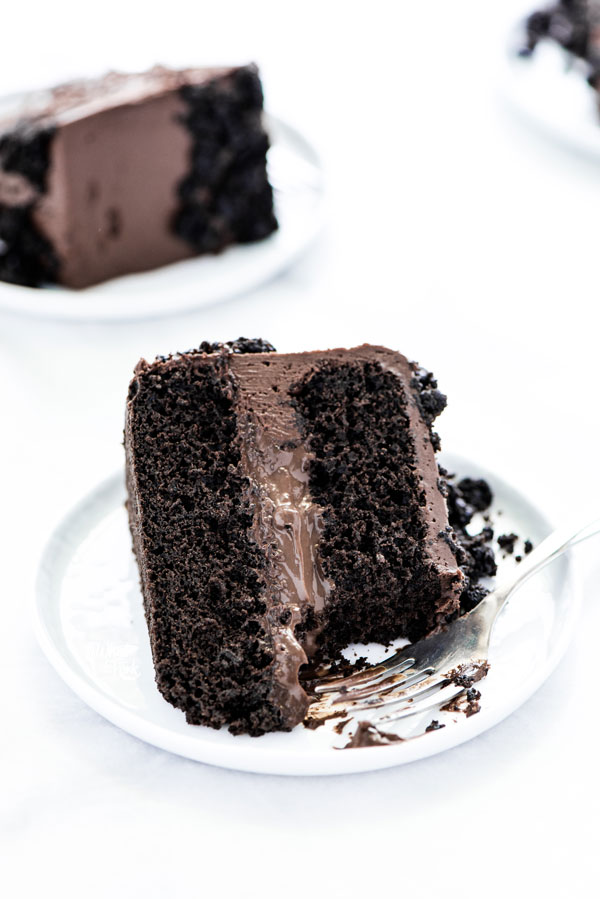 a piece of Gluten Free Brooklyn Blackout Cake on a white plate with a bite taken out