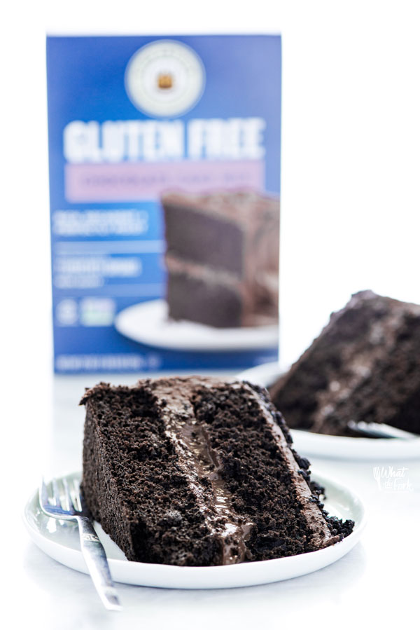 slices of Gluten Free Brooklyn Blackout Cake on white plates with a box of King Arthur Baking Company Gluten Free Chocolate Cake Mix in the background