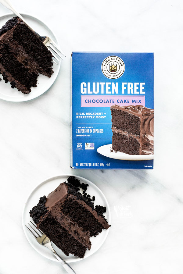 overhead shot of slices of Gluten Free Brooklyn Blackout Cake on white plates around a box of King Arthur Baking Company Gluten Free Chocolate Cake Mix