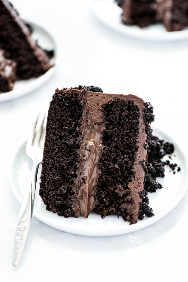 a slice of Gluten Free Brooklyn Blackout Cake on a white plate with a vintage silver fork