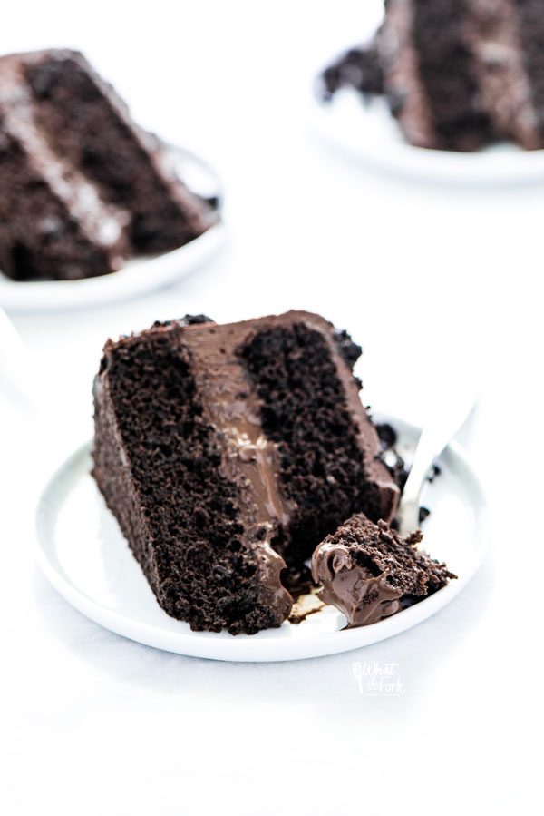 a slice of Gluten Free Brooklyn Blackout Cake on a white plate with a small bite on a silver fork