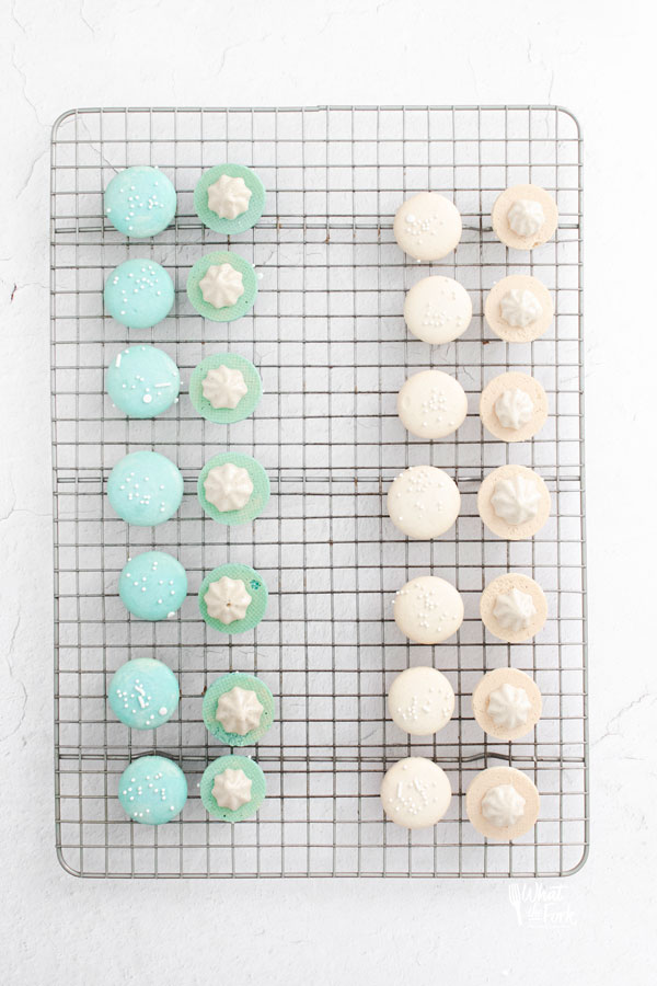 white and blue French Macarons on a wire rack filled and ready to be sandwiched