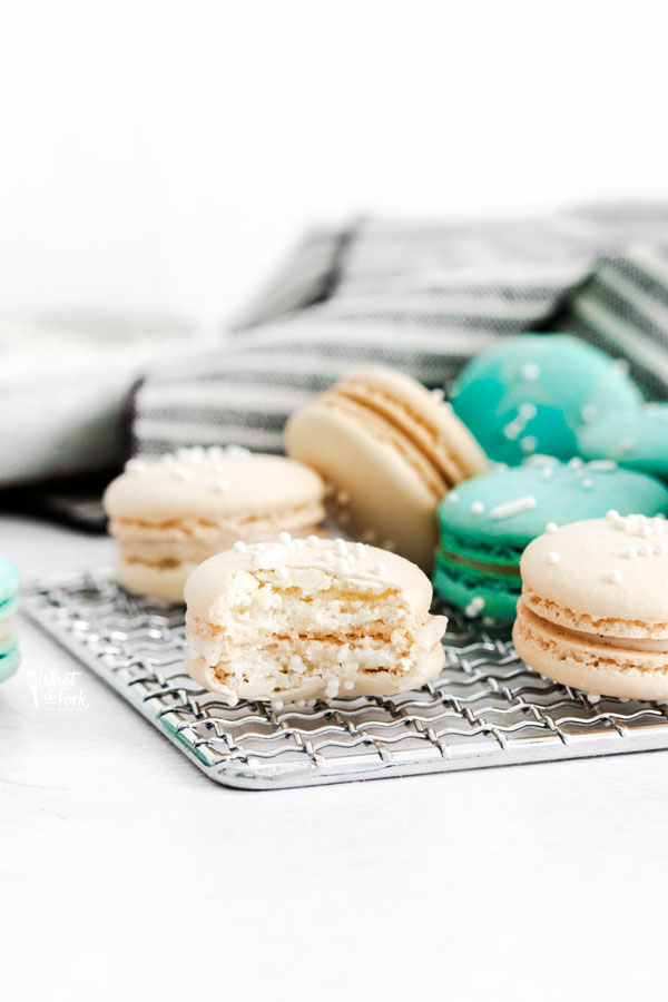 a white macaron on a small wire rack with a bite taken out of it