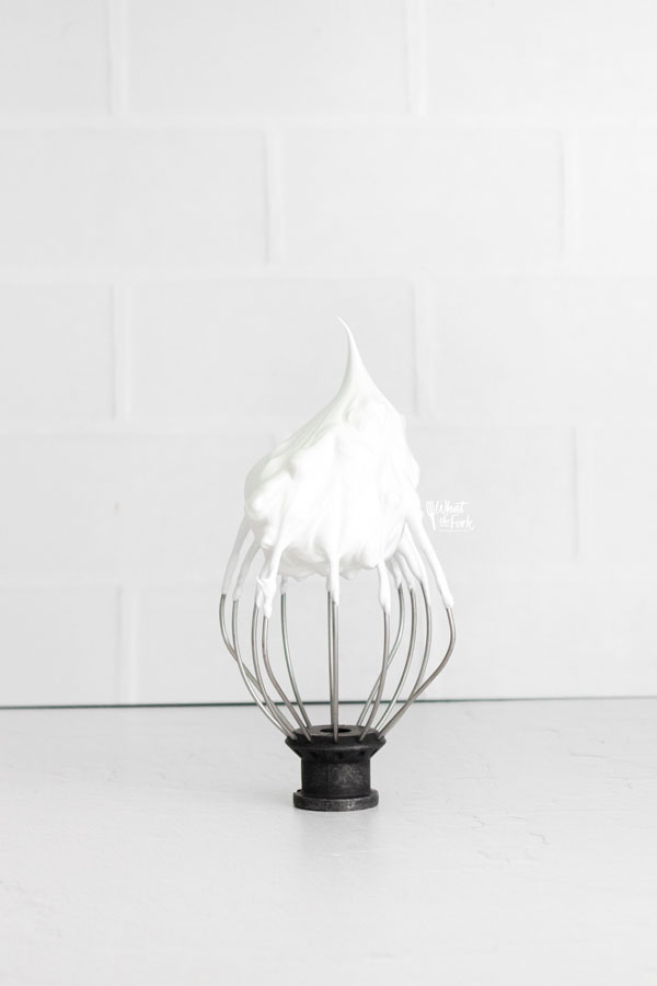 whipped meringue holding a stiff peak on a wire whisk
