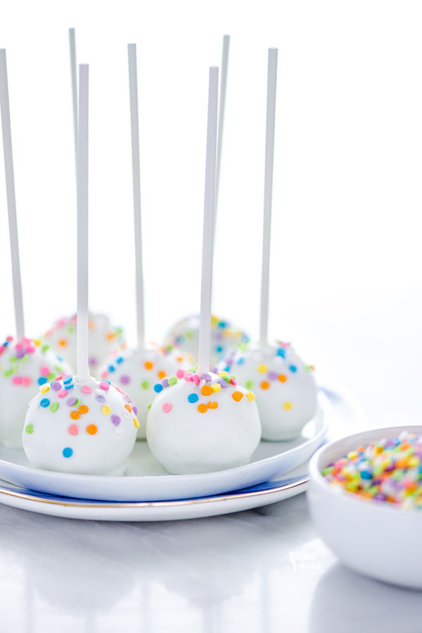 finished gluten free confetti cake pop recipe with cake pops on a stack of white plates ready to be served
