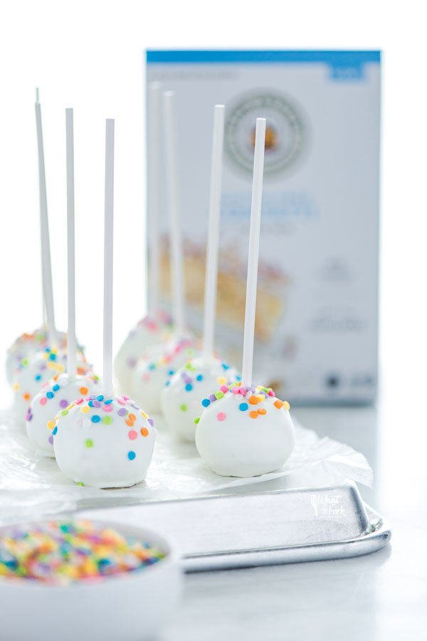 finished Gluten Free Confetti Cake Pop Recipe on an overturned sheet pan lined with wax paper with a box of King Arthur Gluten Free Confetti Cake Mix in the background