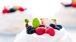 a mini pavlova recipe on a white plate on top of a light wood cutting board. The Mini pavlova is filled with whipped cream and topped with fresh berries and mint