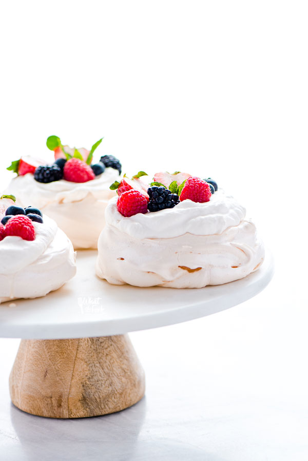 baked and assembled mini pavlovas on a white marble and wood cake stand