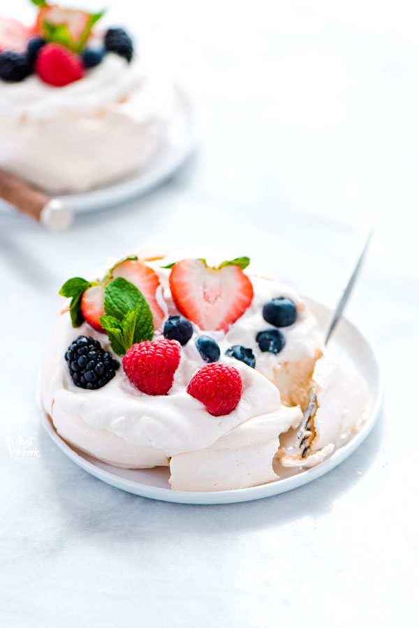 an individual mini pavlova on a small white plate with a fork bite taken out