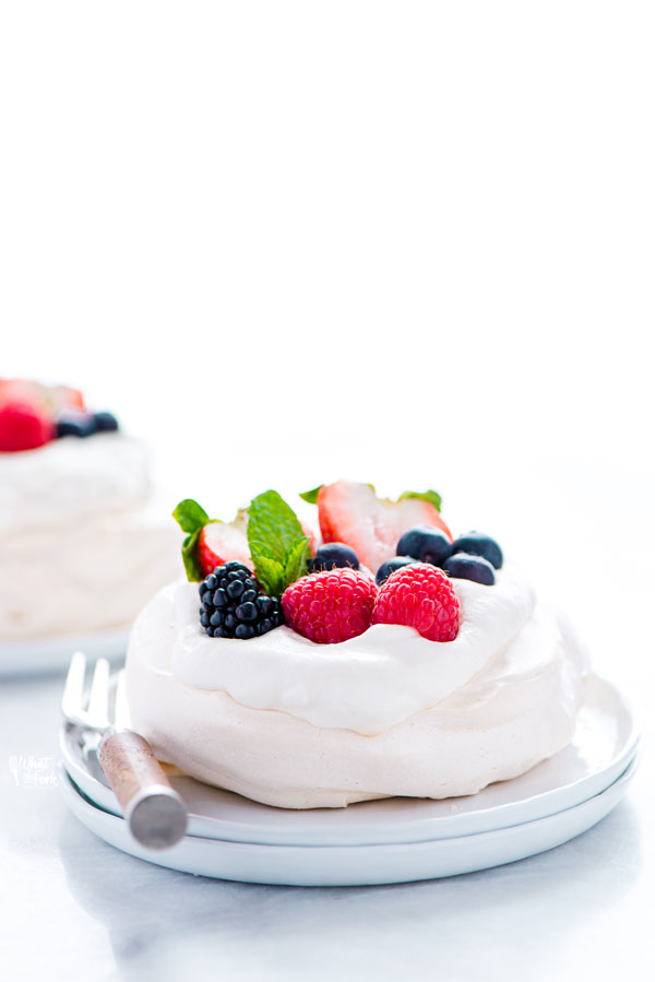 baked and assembled mini pavlova recipe ready to be served on small white plates