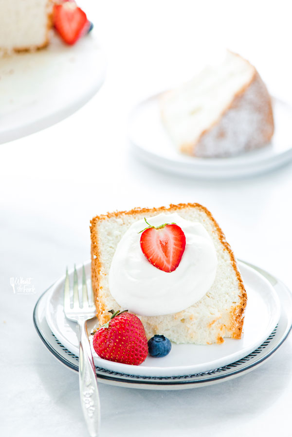 a piece of gluten free angel food cake on a white plate garnished with whipped cream and fresh berries