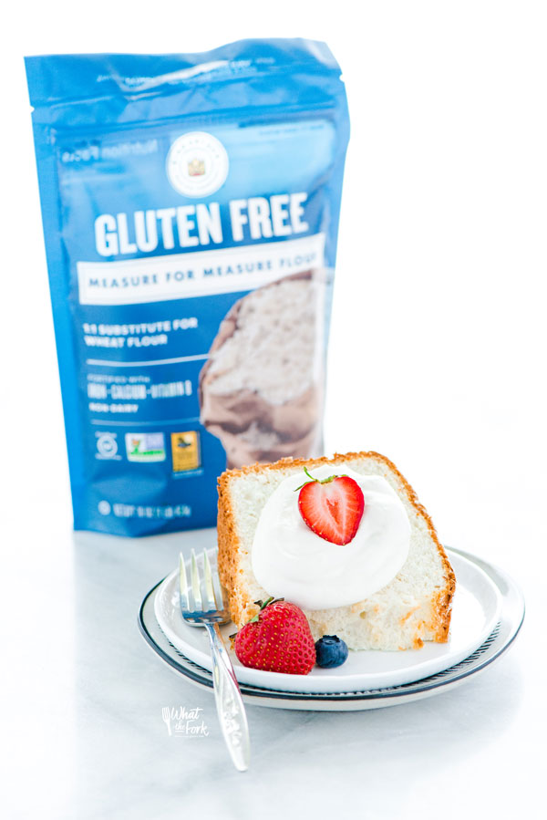 a slice of gluten free angel food cake on a plate with a bag of King Arthur Gluten Free Measure for Measure Flour in the background
