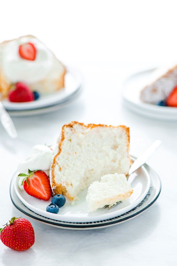 a slice of gluten free angel food cake on a plate garnished with fresh berries and a fork removing a bite
