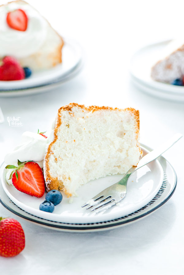 a slice of gluten free angel food cake on a plate with a bite taken out