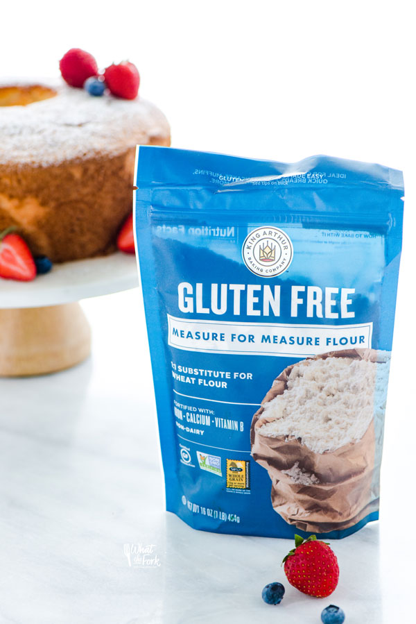 a bag of King Arthur Gluten Free Measure for Measure Flour with a gluten free angel food cake on a cake stand in the background
