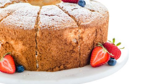 Gluten Free Angel Food Cake on a white and wood cake stand garnished with fresh berries and dusted with powdered sugar