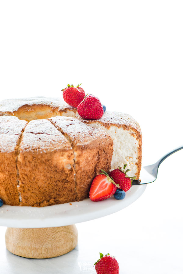 A slice of guten free angel food cake being removed from a cake stand with a black cake server