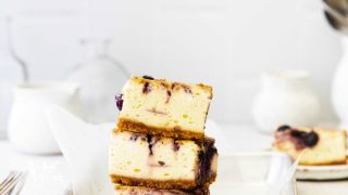 3 Gluten Free Blueberry Cheesecake Bars stacked on a 1/8 sheet pan lined with white parchment paper