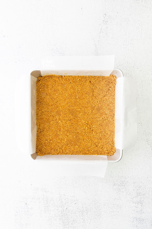 graham cracker crust in an 8x8 square metal pan lined with parchment paper