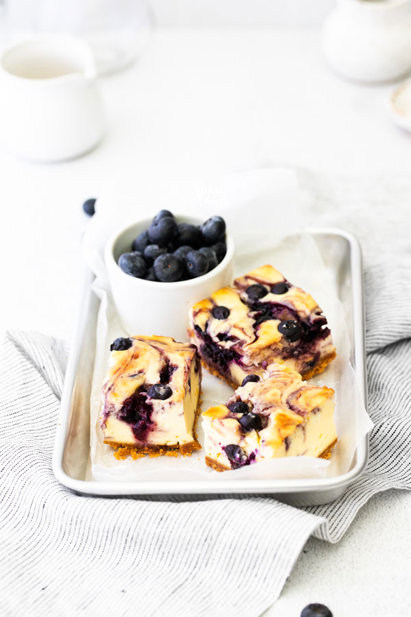 3 Gluten Free Blueberry Cheesecake Bars on a parchment paper lined 1/8 sheet pan