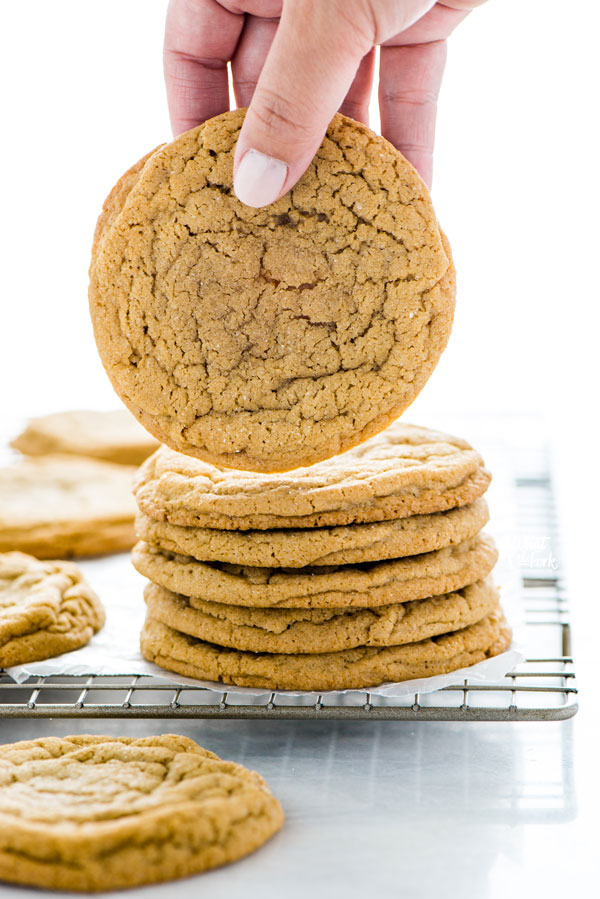 a hand picking up a Gluten Free Brown Sugar Cookie from a stack of cookies on a wire rack