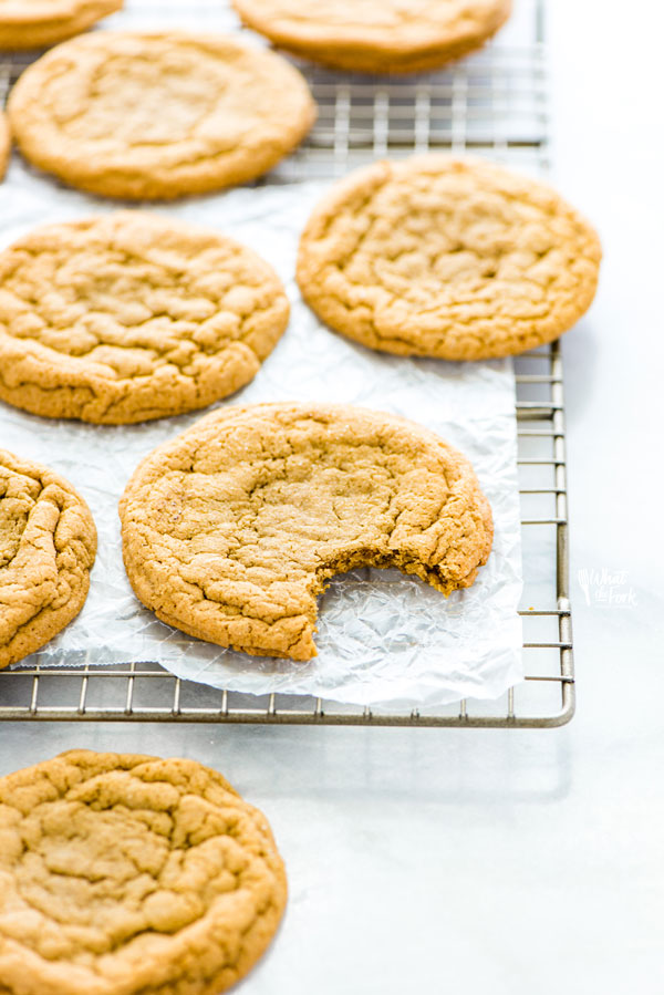 Gluten Free Brown Sugar Cookies on a wire rack, one with a bite taken out