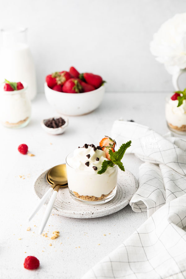 Cheesecake Mousse in a glass bowl on a pottery plate with gold and white spoons