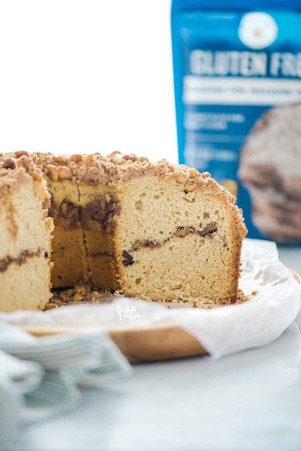 gluten free sour cream coffee cake sliced into with a bag of King Arthur Gluten Free Measure for Measure Flour in the background