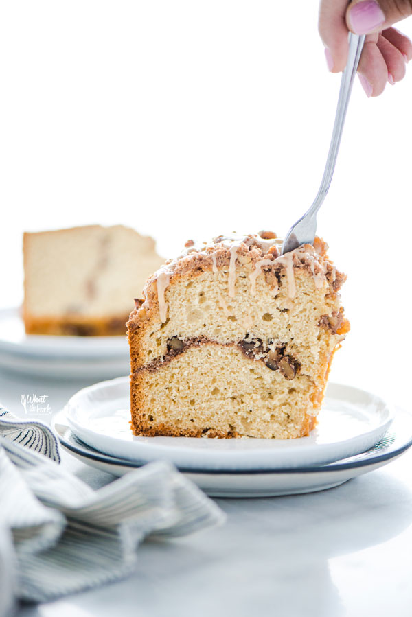 a slice of gluten free sour cream coffee cake on a plate with a fork taking a piece out