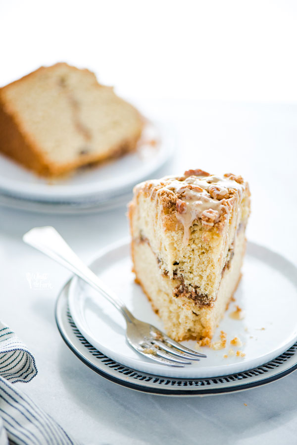 a slice of gluten free sour cream coffee cake on a white plate with a fork that has a bite taken out