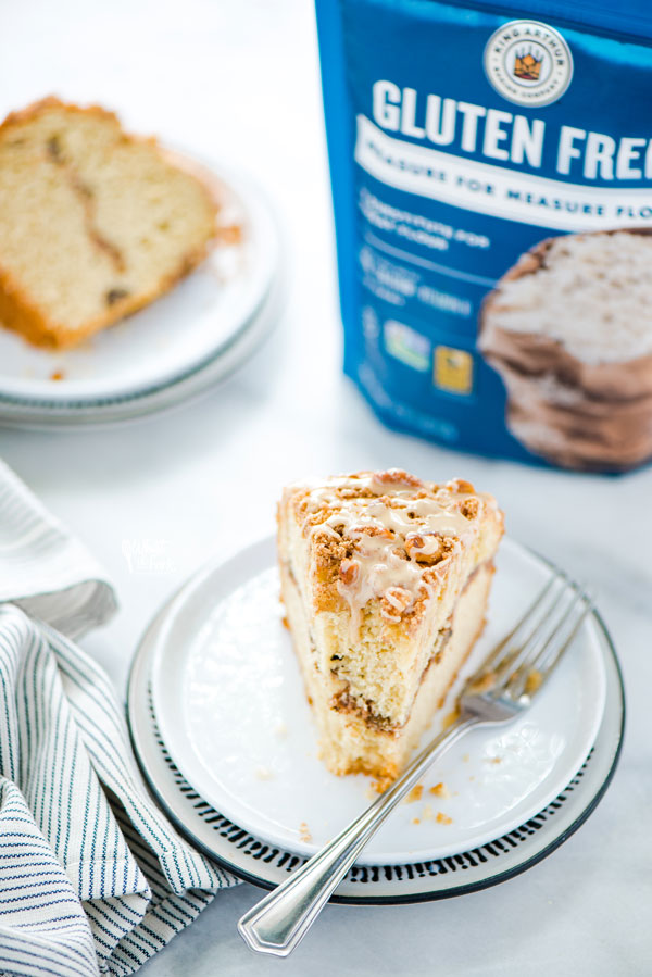 a slice of gluten free sour cream coffee cake on a white plate with a bag of King Arthur Gluten Free Measure for Measure Flour in the background