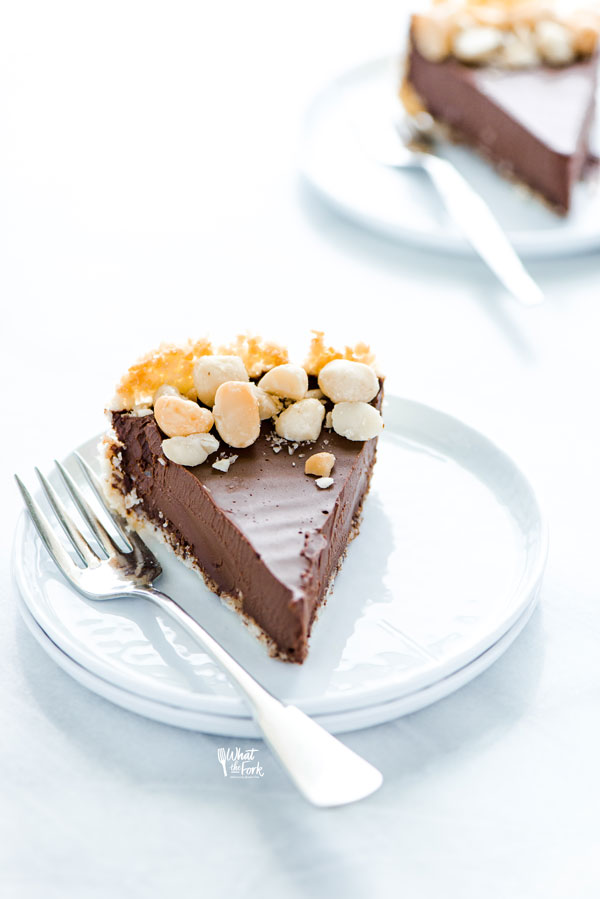 a slice of Macadamia Nut Chocolate Pie with Coconut Crust on a stack of 2 white plates with a silver fork