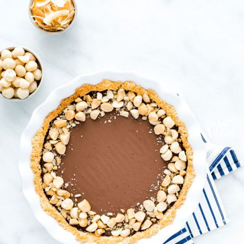 overhead shot of a Macadamia Nut Chocolate Pie with Coconut Crust on a blue and white striped cloth napkin