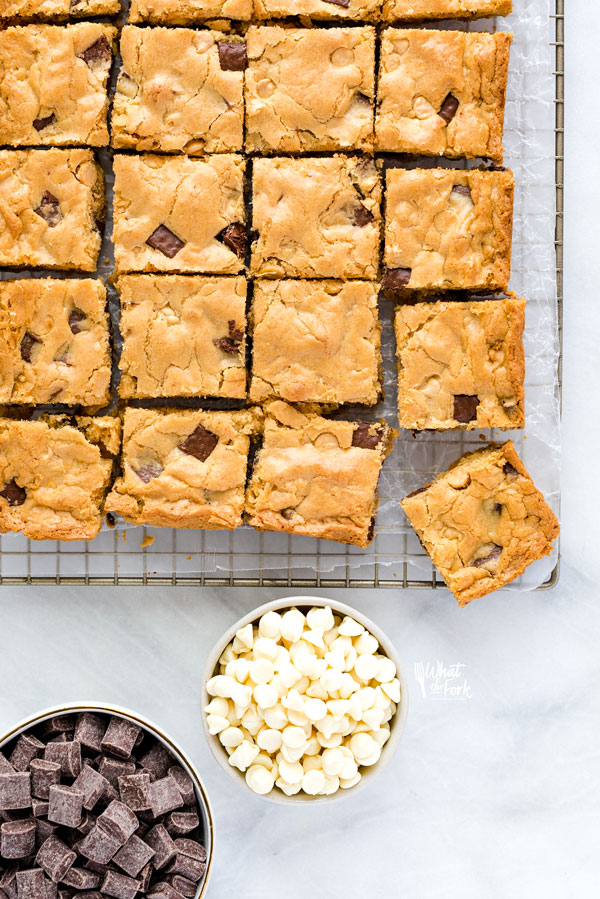 overhead shot of gluten free blondies on a cooling rack with bowls of white chocolate chips and chocolate chunks