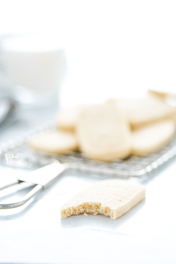 a shortbread cookie on a marble surface with a bite taken out
