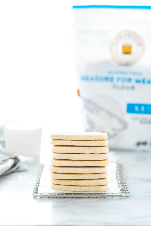 a stack of Gluten Free Shortbread Cookies on a small metal wire rack lined with wax paper with a bag of King Arthur Gluten Free Measure for Measure Flour in the background